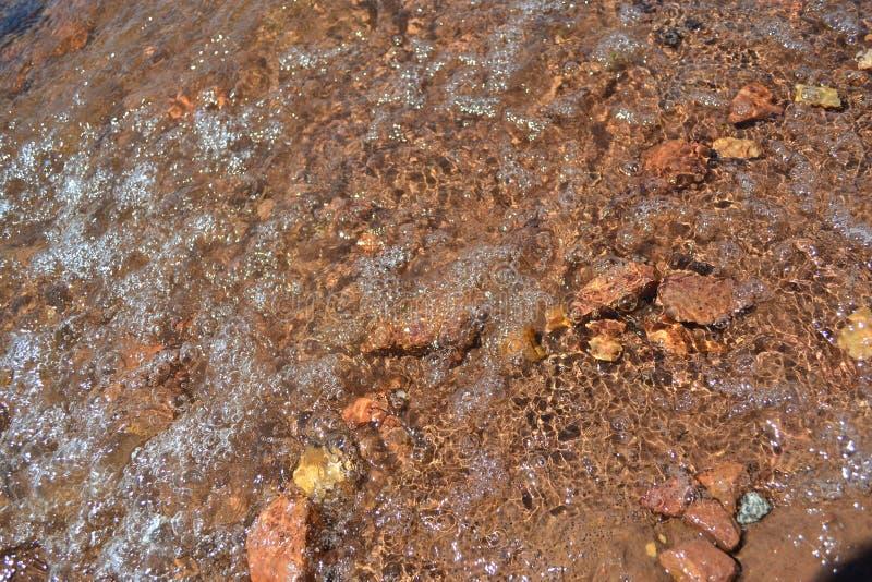 Детализирует разносторонние камни в воде озера стоковые изображения