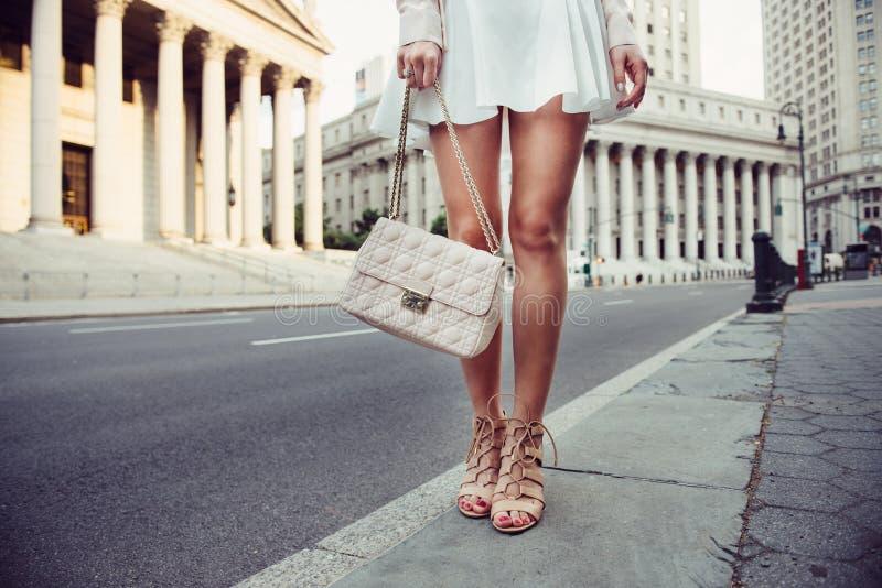 Детали крупного плана улицы лета женской вскользь вводят обмундирование в моду с роскошными сумкой, юбкой и высоко-пятками Модная стоковые фотографии rf