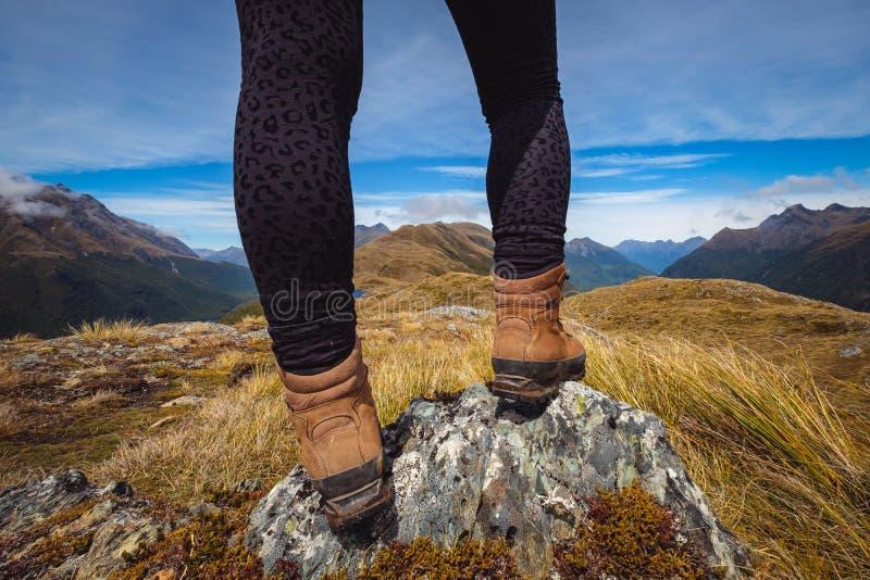 Деталь ног ` s женщины в trekking ботинках с предпосылкой горной цепи стоковые изображения rf