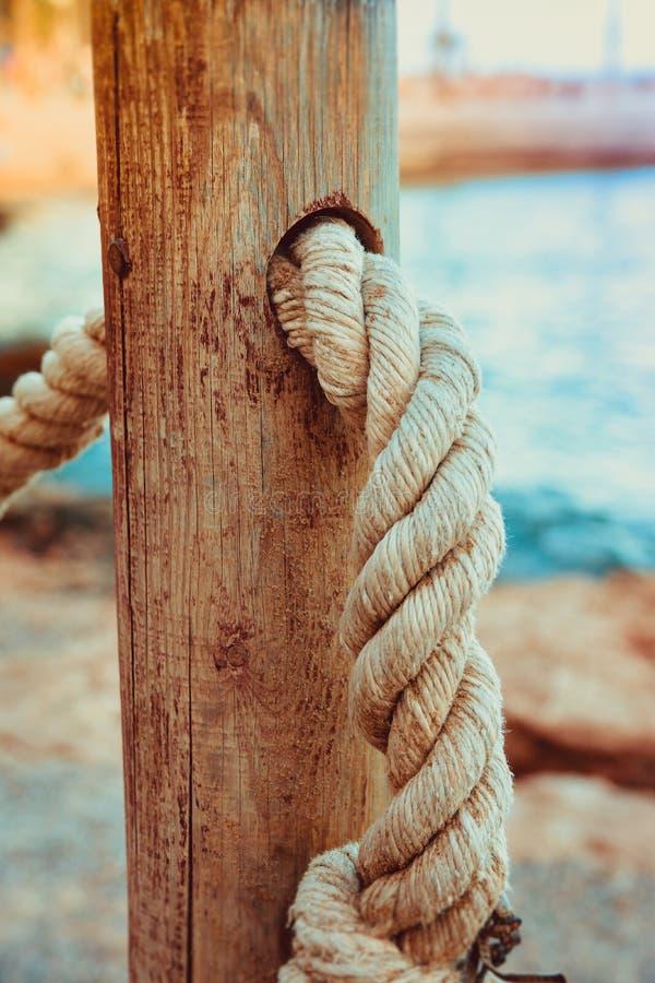 Деталь перил веревочки дорожки пляжа, старого деревянного поляка, голубого песка моря на заднем плане, каникулы взморья стоковое изображение rf