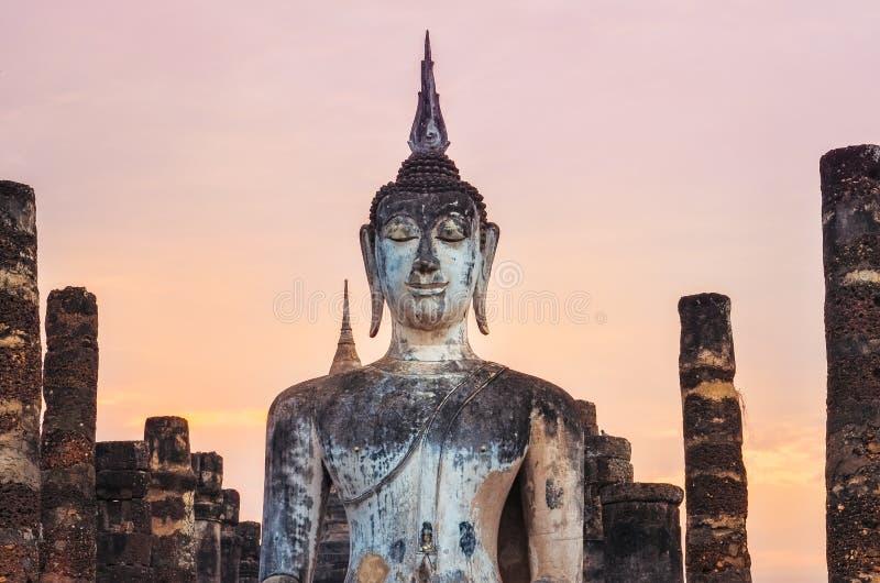 Деталь сидеть Будда на красочном заходе солнца, Sukhothai, Таиланд стоковое фото