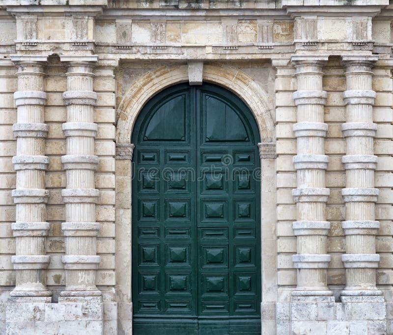 Деталь старого городского фасада камня здания с высокорослой дверью древесной зелени и декоративными столбцами стоковая фотография