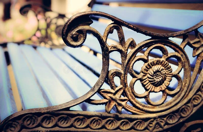 Деталь старой скамейки в парке с орнаментами, предпосылки bokeh стоковые изображения rf