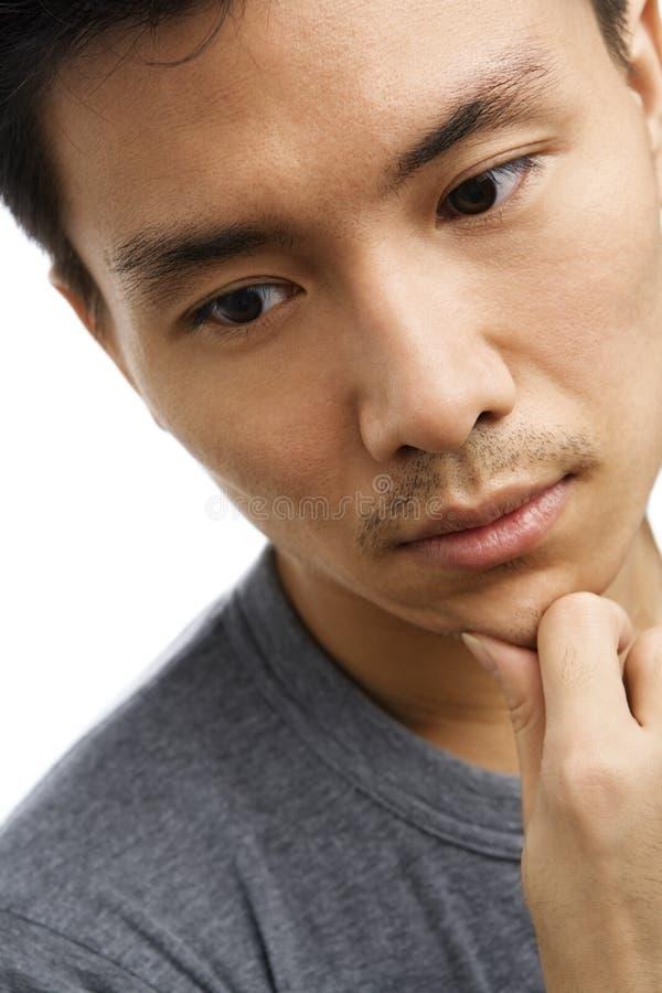 детеныши азиатского человека выражения унылые стоковое изображение rf