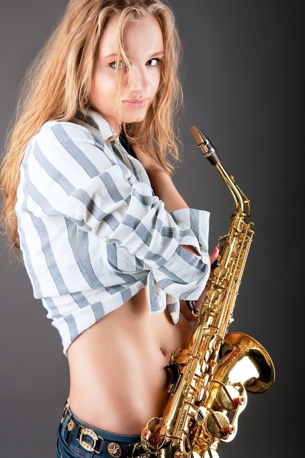 детеныши белокурого саксофона девушки милого сексуальные стоковое фото rf