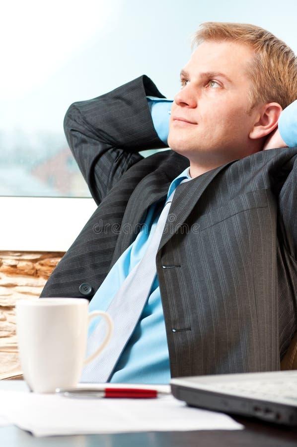 детеныши бизнесмена отдыхая удовлетворенные стоковая фотография