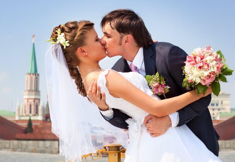 детеныши венчания пар целуя стоковая фотография rf
