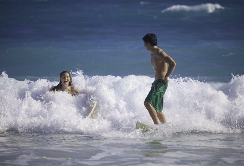 детеныши Гавайских островов пар занимаясь серфингом стоковые фотографии rf