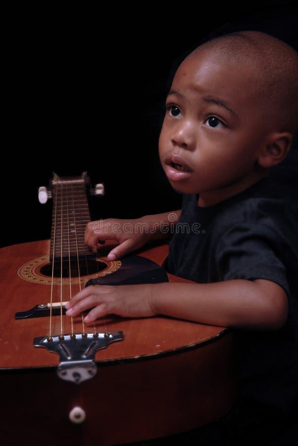 детеныши гитары мальчика стоковое фото