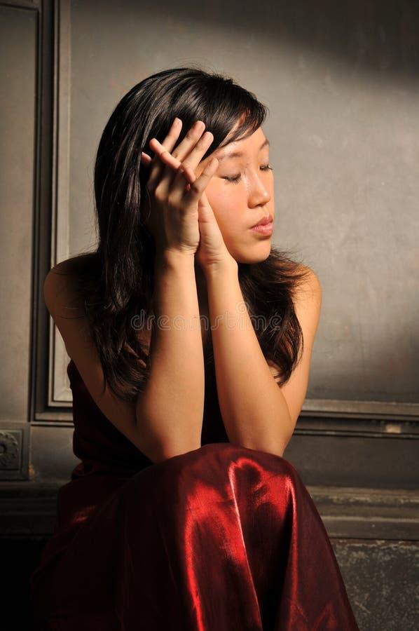 детеныши женщины азиатского красивейшего ощупывания унылые стоковая фотография rf