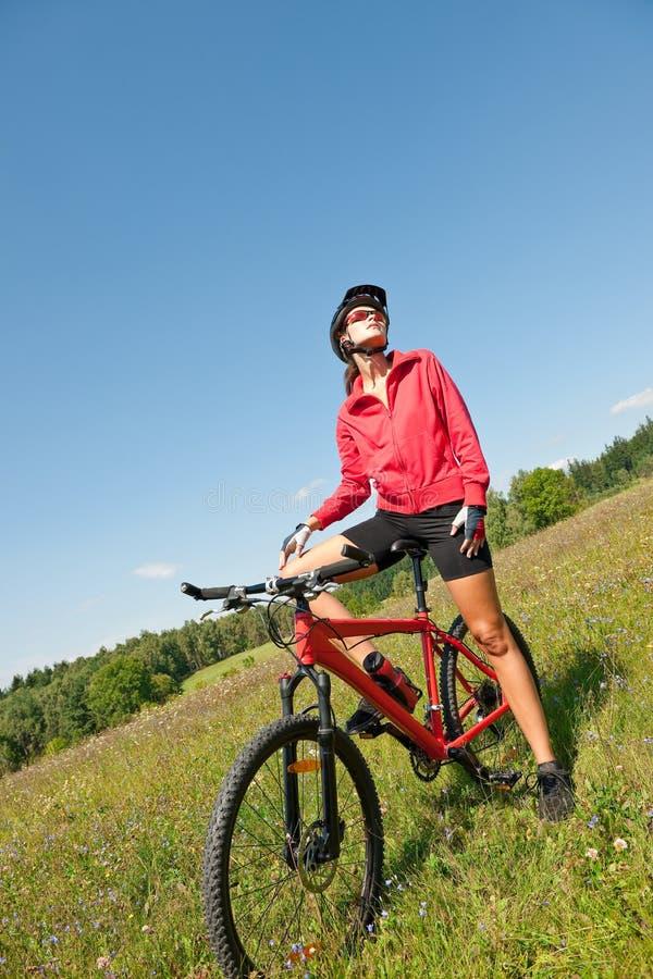 детеныши женщины весны лужка bike sportive стоковая фотография rf
