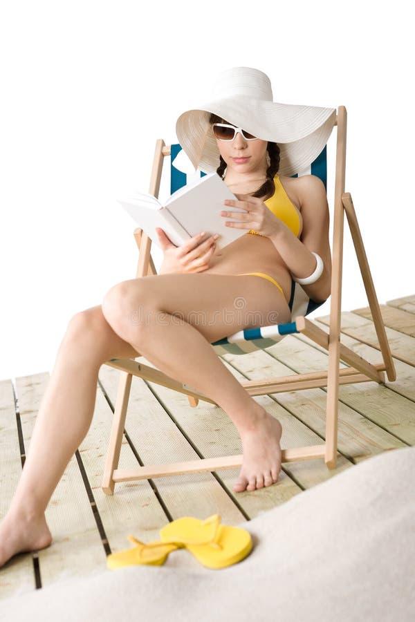 детеныши женщины книги бикини пляжа sunbathing стоковые изображения