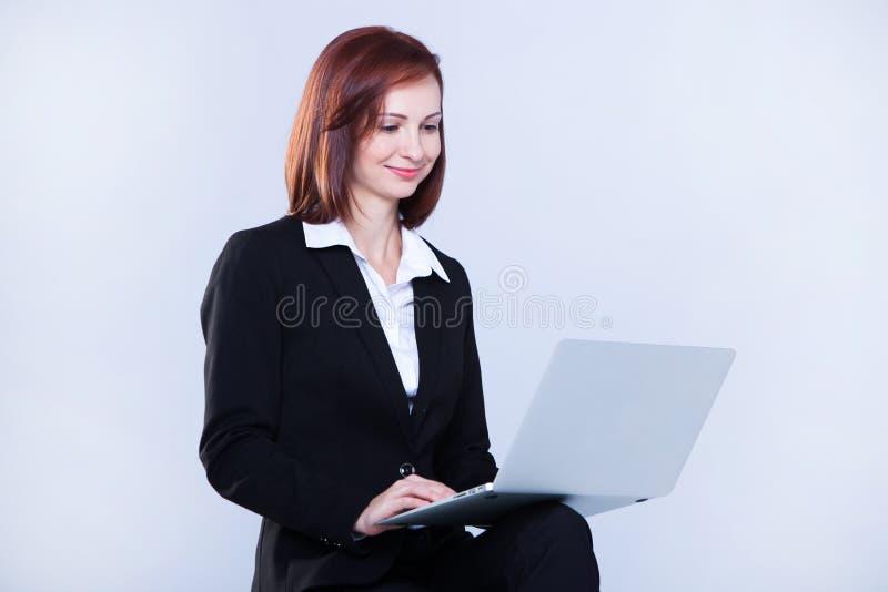 детеныши женщины компьтер-книжки дела работая Привлекательная зрелая коммерсантка работая на ноутбуке стоковые изображения