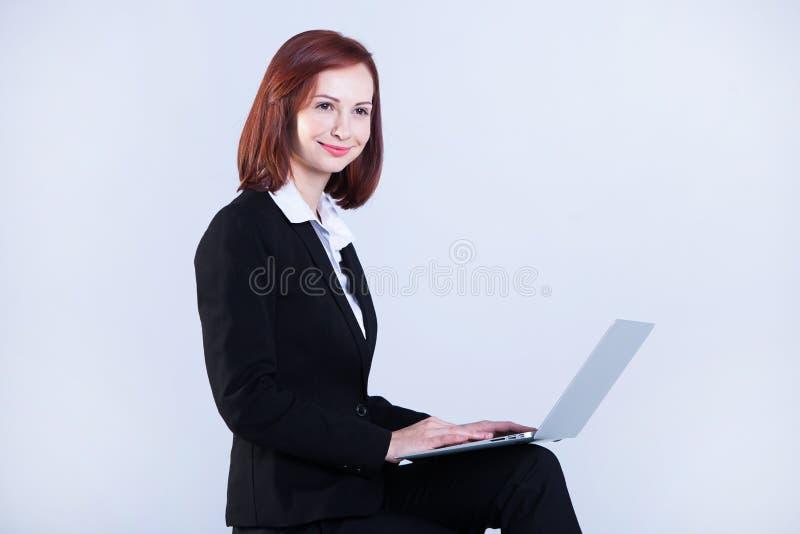 детеныши женщины компьтер-книжки дела работая Привлекательная зрелая коммерсантка работая на ноутбуке стоковое фото rf