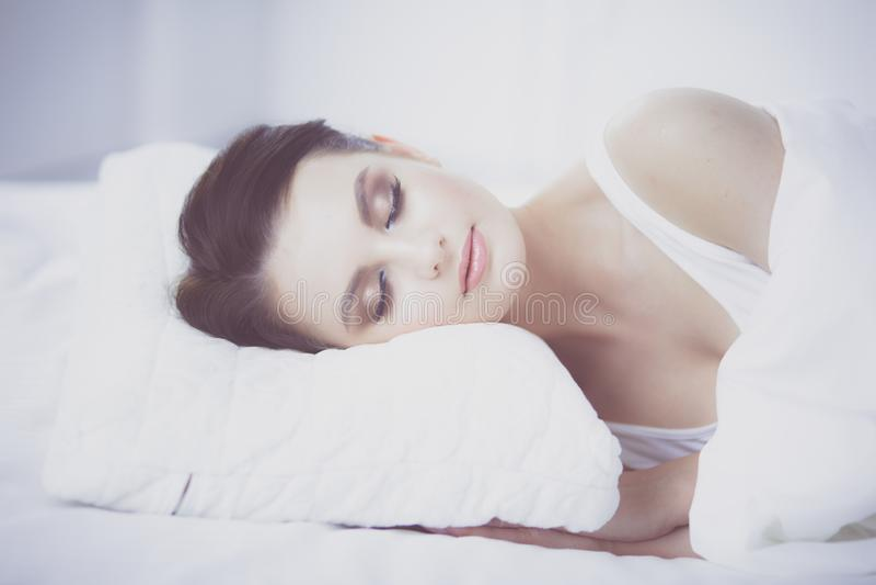 детеныши женщины красивейшей кровати лежа стоковое изображение rf