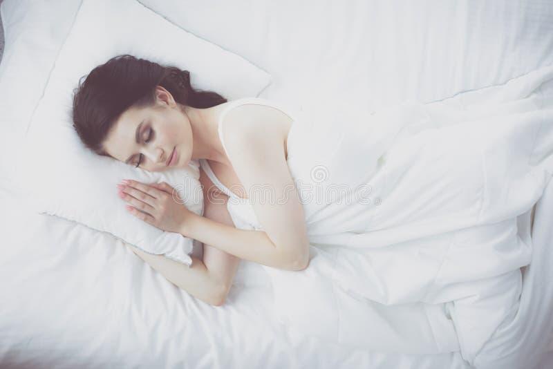 детеныши женщины красивейшей кровати лежа стоковое изображение