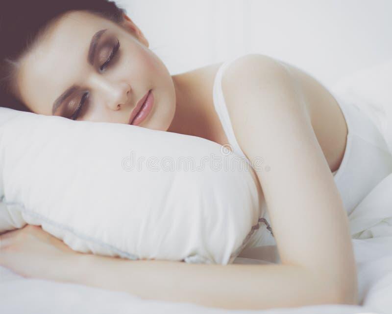 детеныши женщины красивейшей кровати лежа стоковые фото