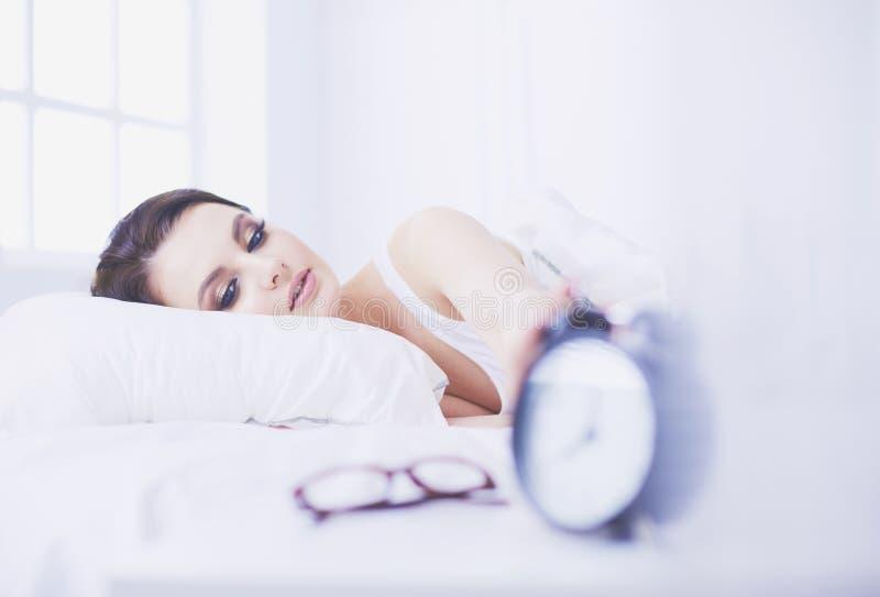 детеныши женщины красивейшей кровати лежа стоковое фото