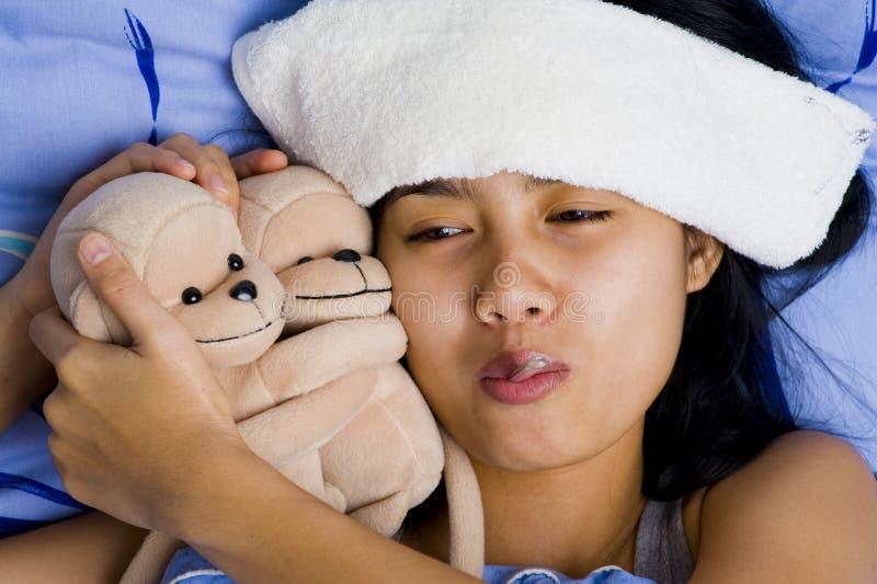 детеныши женщины кровати довольно больные стоковые изображения
