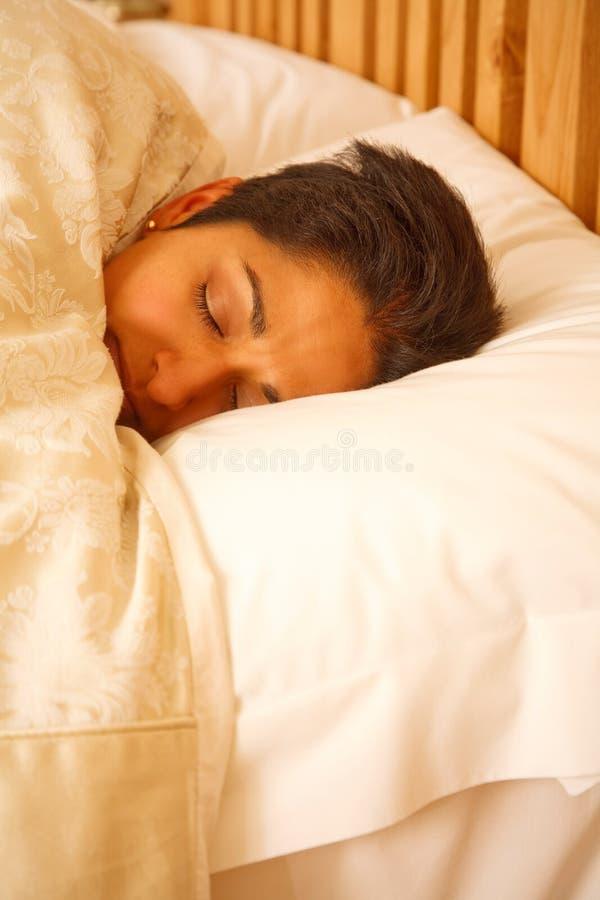 детеныши женщины кровати стоковое изображение