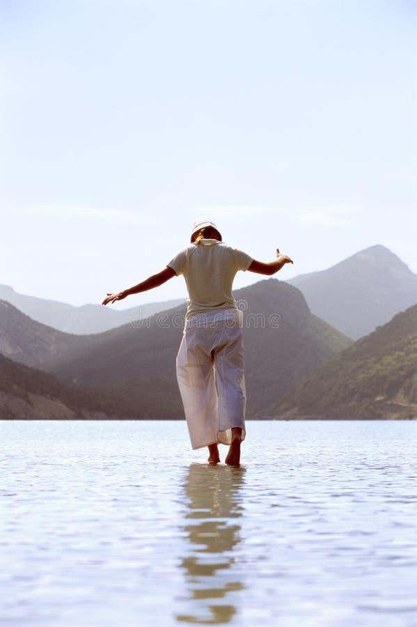 детеныши женщины озера гуляя стоковая фотография