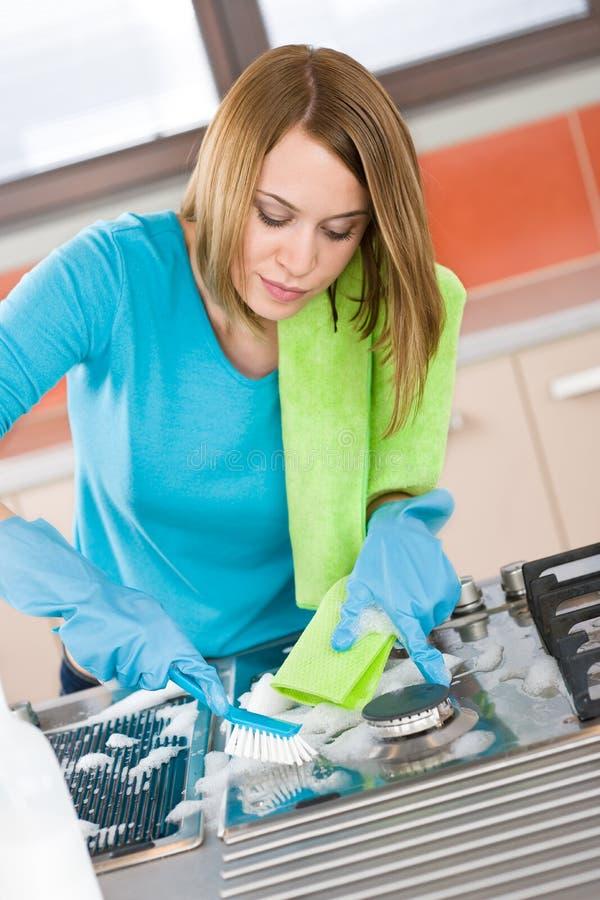 детеныши женщины печки кухни чистки стоковое фото