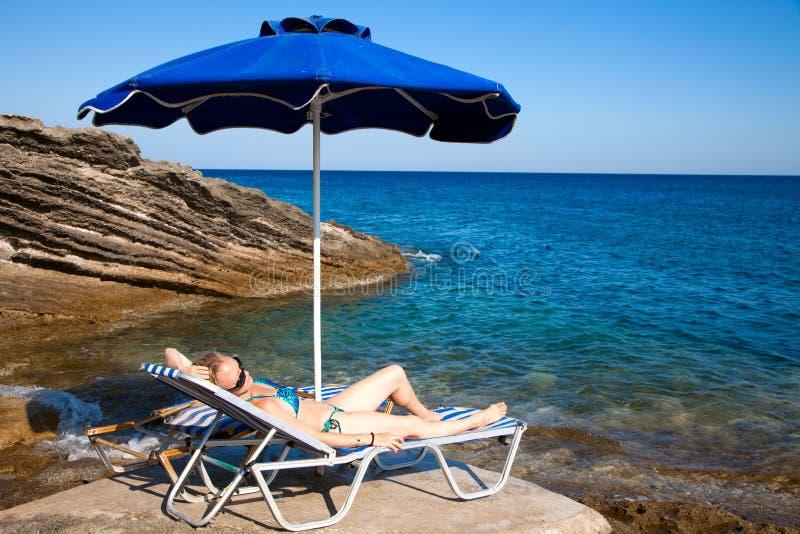 детеныши женщины пляжа ослабляя стоковое фото