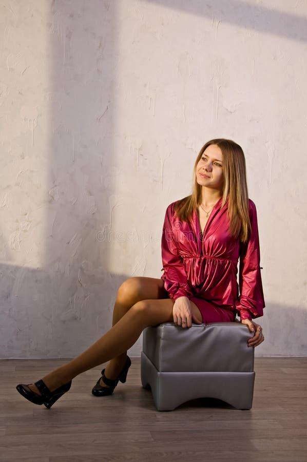 детеныши женщины привлекательного стула серые сидя стоковые изображения