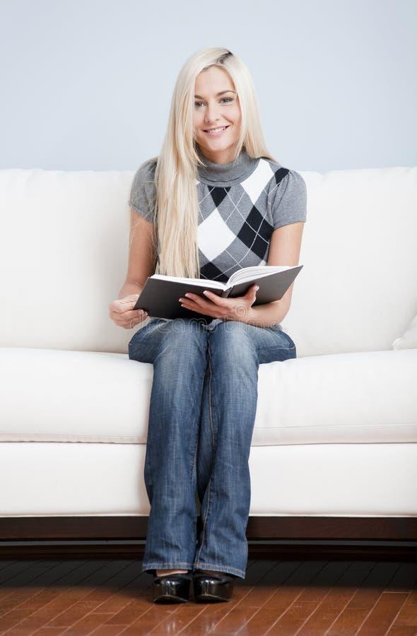 детеныши женщины софы удерживания книги открытые сидя стоковое изображение