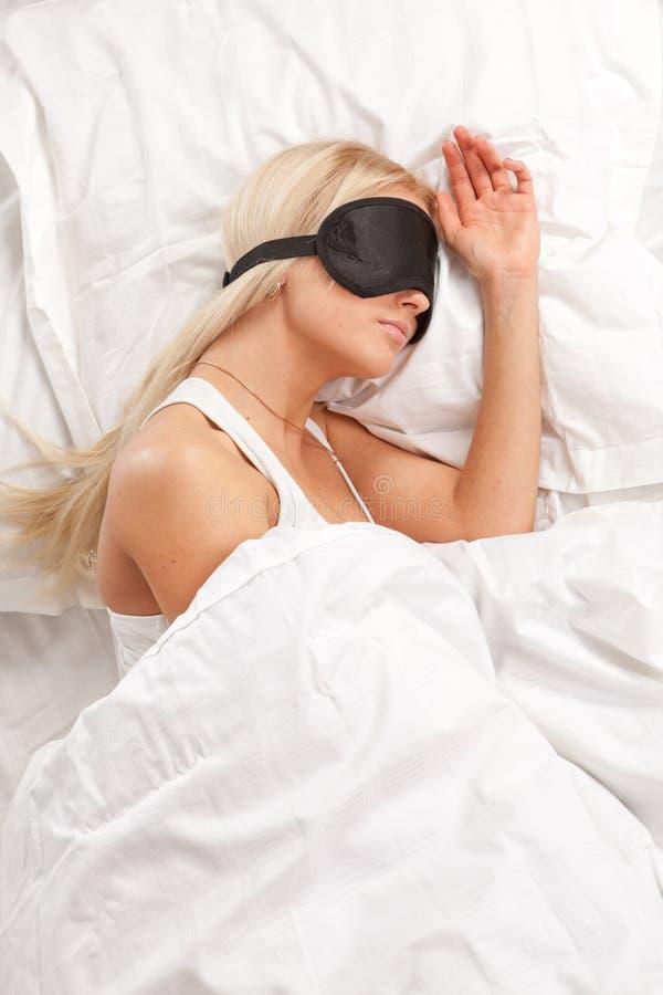 детеныши женщины спать кровати стоковое изображение