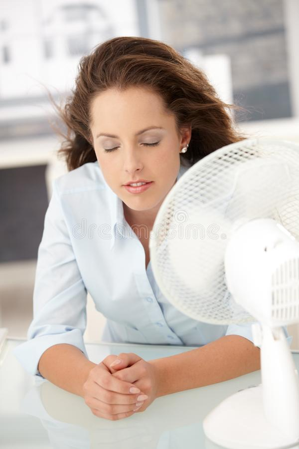 детеныши женщины фронта себя охлаждающего вентилятора сидя стоковые изображения