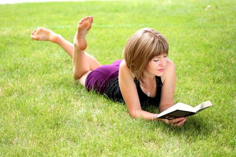 детеныши женщины чтения книги счастливые стоковое изображение rf