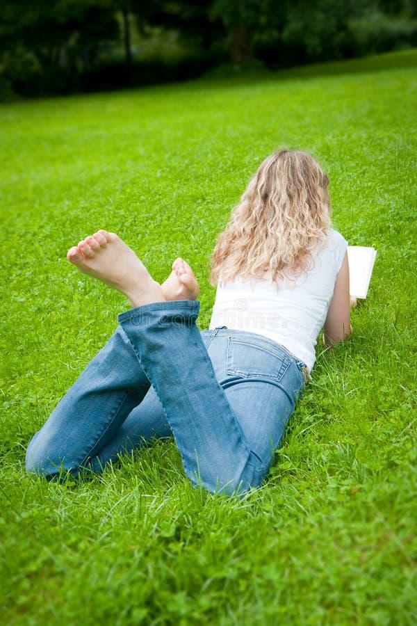 детеныши женщины чтения парка белокурой книги курчавые стоковая фотография