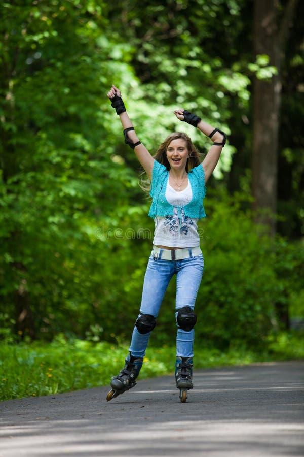 детеныши женщины rollerskating стоковое фото
