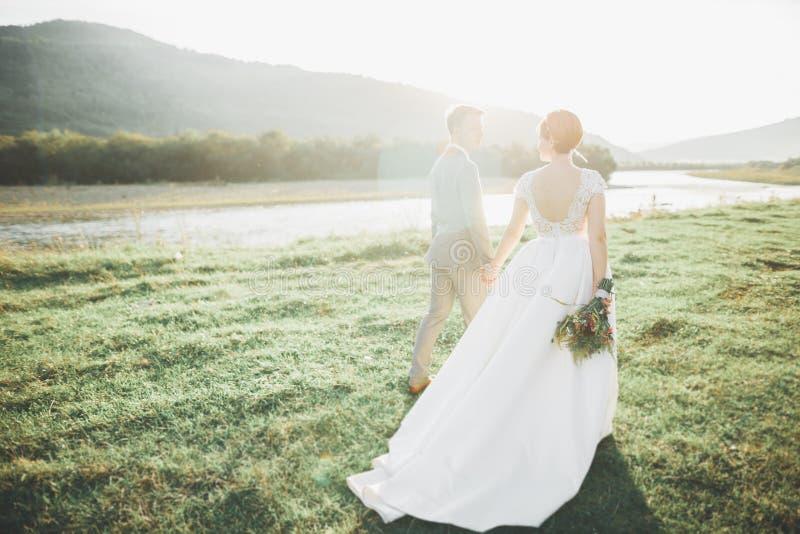 Детеныши заново wed пары, целовать жениха и невеста, обнимая на совершенном взгляде гор, голубое небо стоковое изображение rf