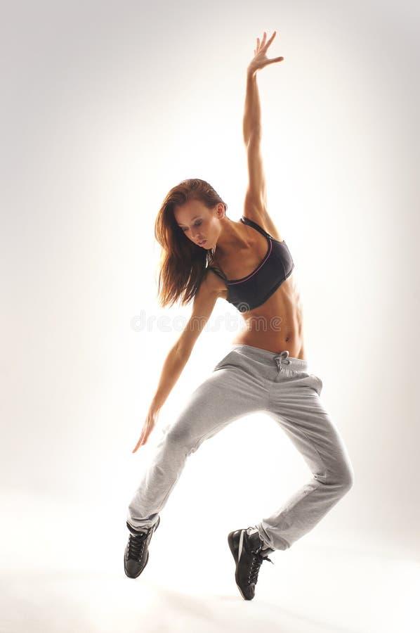 Детеныши и танцор пригонки женский в sporty одеждах стоковые фото