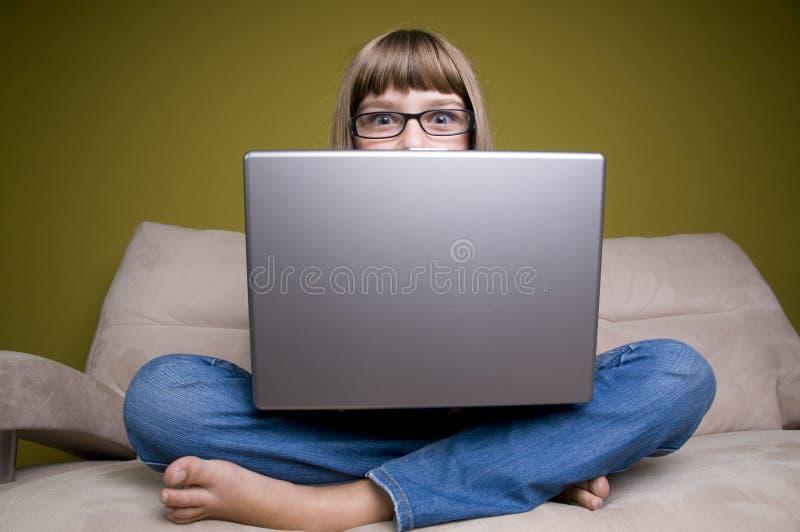 детеныши компьтер-книжки девушки кресла стоковое изображение