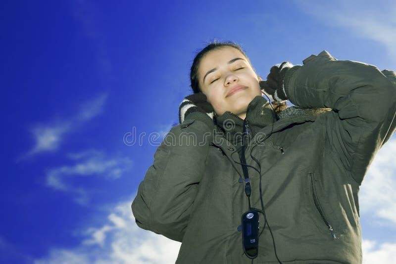 детеныши нот красивейшей девушки слушая стоковое фото