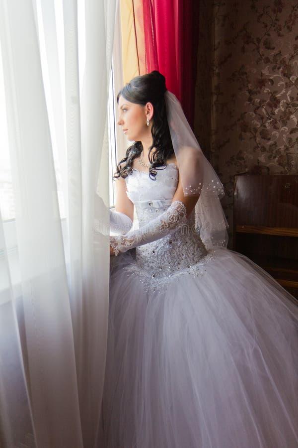 детеныши окна красивейшей невесты стоящие стоковое изображение rf