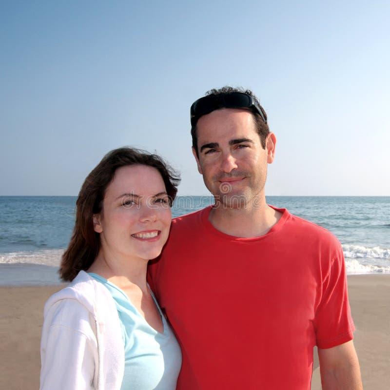 детеныши пар пляжа счастливые стоковое изображение