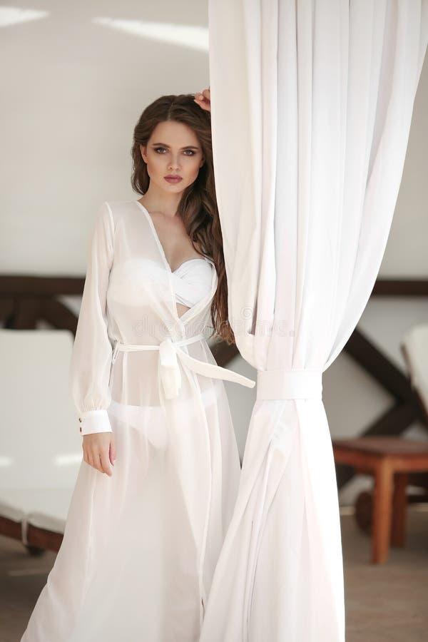 детеныши портрета красивейшей девушки напольные Брюнет arefree ¡ Ð нося в шифоновом платье носки белым занавесом на гостиной пляж стоковая фотография