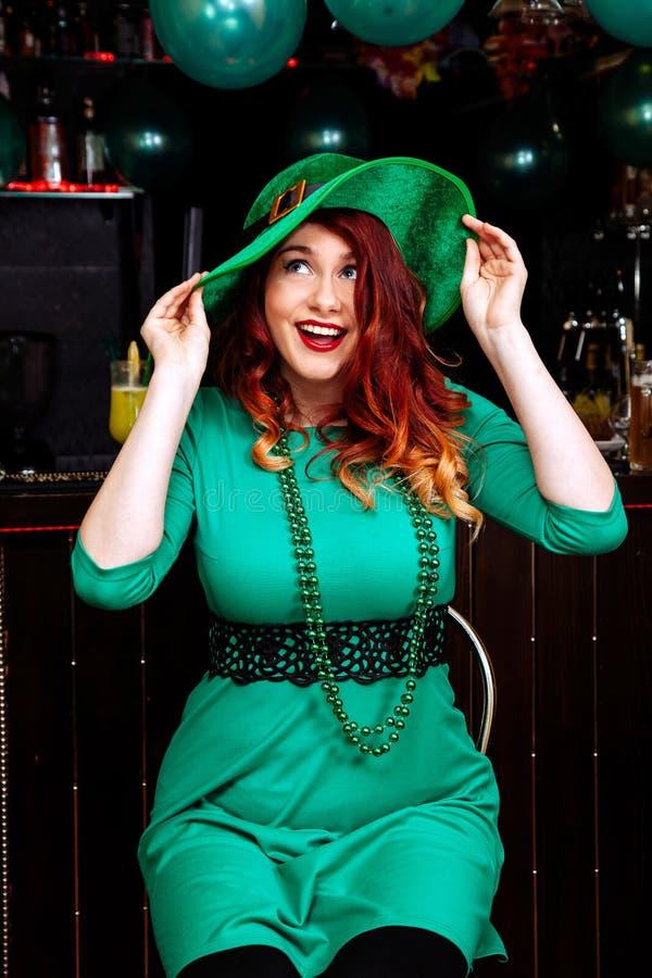Детеныши празднуют лепрекона улыбки шляпы одежд зеленого цвета коктеиля пива человека девушки headgear масленицы бара потехи дня  стоковое изображение rf