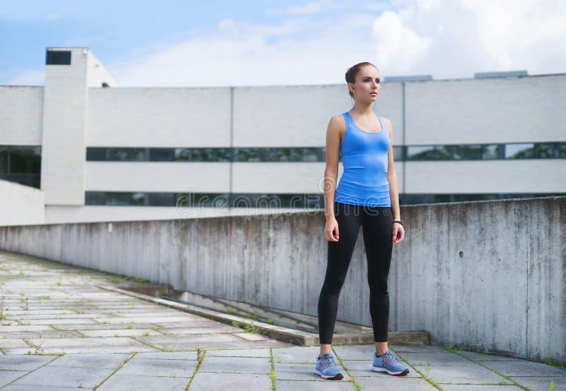 Детеныши, пригонка и sporty женщина стоя перед конкретной стеной цемента Фитнес, спорт, городской jogging и здоровый стоковые фото