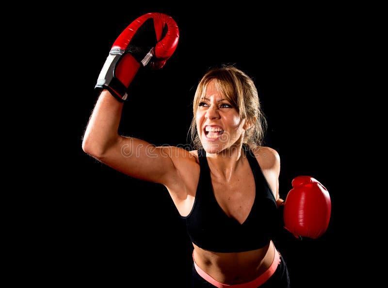 Детеныши приспособленные и сильная привлекательная девушка боксера с красными перчатками бокса воюя бросая агрессивную разминку т стоковое фото rf