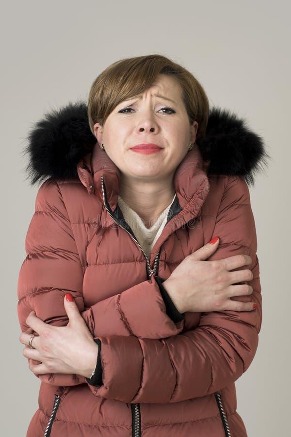 Детеныши прочитали женщину 20s или 30s волос привлекательную и сладостную представляя нося теплую куртку зимы с знобить и freez к стоковые изображения