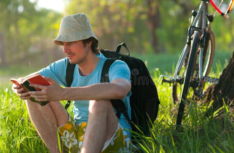 детеныши путешественника чтения книги велосипеда стоковые фотографии rf