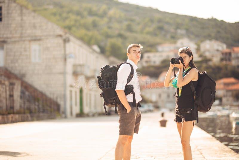 Детеныши работать фотографы путешествуя и укладывая рюкзак Испытывать различные культуры, фотожурналистика Репортажно-документаль стоковая фотография rf