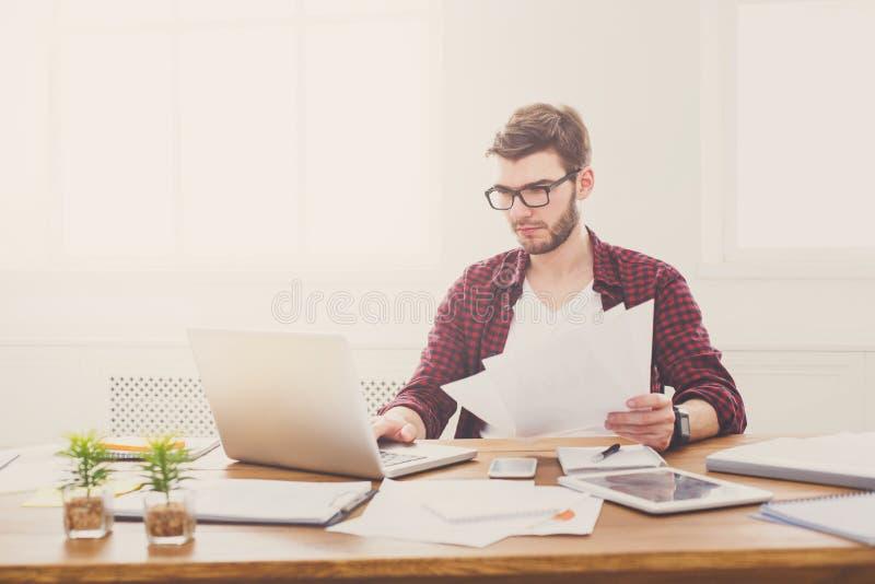 Детеныши сконцентрировали бизнесмена используя компьтер-книжку в современном белом офисе стоковое изображение rf