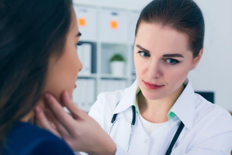 Детеныши сконцентрировали лимфоузлы женского доктора ощупывая пациента Доктор касаясь горлу пациента стоковая фотография rf