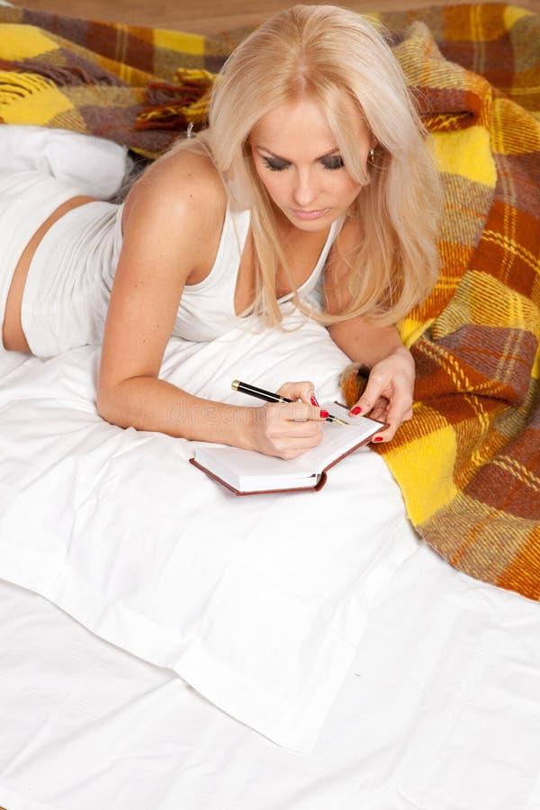 детеныши сочинительства женщины th дневника лежа стоковое фото